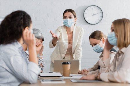 junger Teamleiter in medizinischer Maske zeigt mit der Hand auf interrassische Geschäftsfrauen im verschwommenen Vordergrund