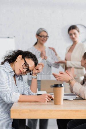 Photo pour Femme d'affaires afro-américaine assise au bureau près de collègues sur fond flou - image libre de droit