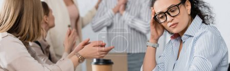 African american businesswoman looking at paper cup near coworkers on blurred background, banner