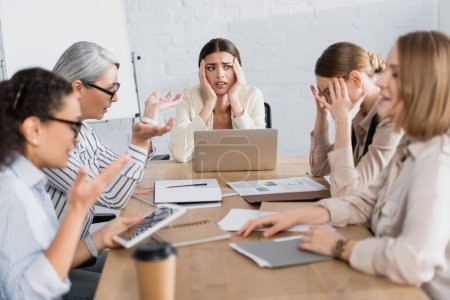 worried interracial businesswomen discussing problem during meeting in office