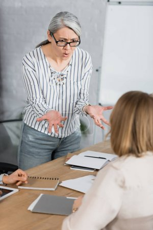 displeased asian businesswoman gesturing while talking with coworker in office