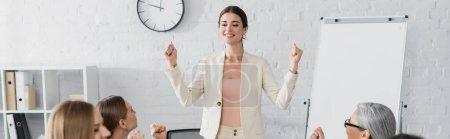 Photo pour Chef d'équipe souriant debout avec les poings serrés près du public multiculturel sur le premier plan flou, bannière - image libre de droit