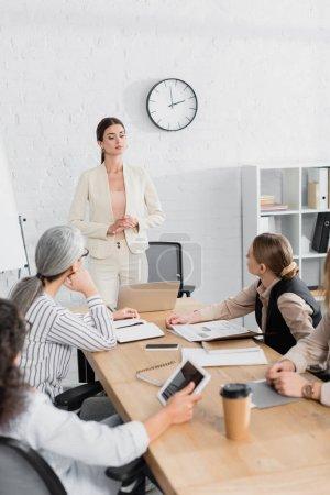 team leader standing near multiethnic businesswomen during meeting in office