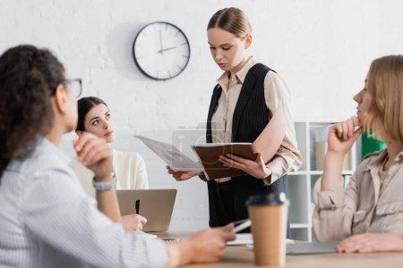 junge Geschäftsfrau hält Ordner in der Nähe von Teamleiter und multikulturellen Mitarbeitern während eines Treffens