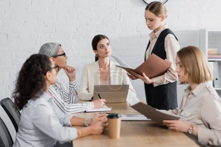 young businesswoman holding folder near team leader and interracial coworkers during meeting
