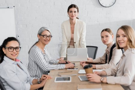 team leader standing near happy multiethnic businesswomen during meeting in office