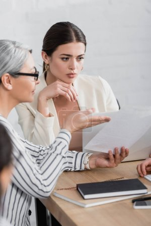 asian businesswoman pointing with hand at document near colleague in office