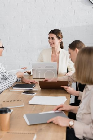 asian businesswoman giving document to happy team leader near coworkers in office