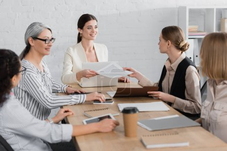 happy team leader giving document to coworker near multicultural businesswomen during meeting