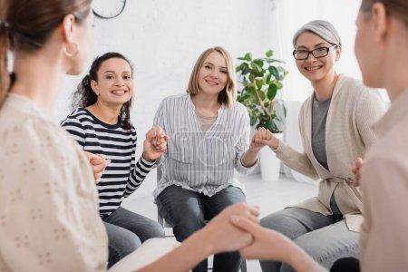 heureuses femmes multiculturelles se tenant la main pendant le séminaire