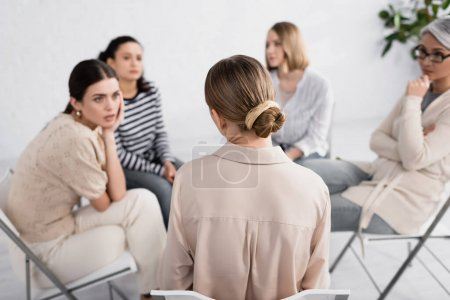 back view of woman sitting on chair near multicultural female group during seminar
