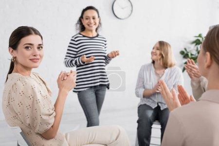 Photo pour Jeune femme applaudissant et regardant la caméra près de haut-parleur afro-américain debout sur fond flou - image libre de droit