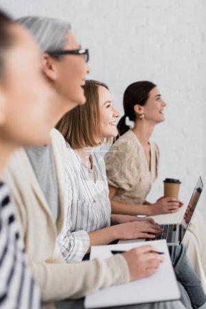 mujer alegre sonriendo cerca de grupo multicultural de mujeres durante el seminario en primer plano borroso y fondo