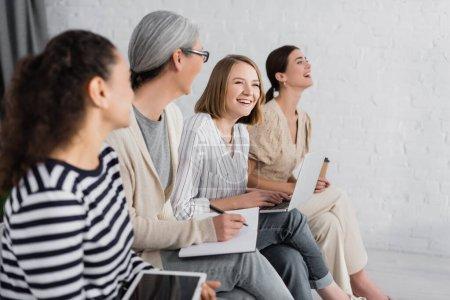 Photo pour Femmes d'affaires multiculturelles souriant tout en tenant des gadgets pendant le séminaire - image libre de droit