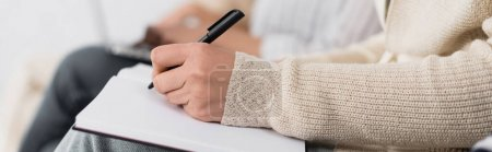 partial view of businesswoman writing in notebook during seminar, banner