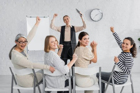 excited interracial businesswomen and speaker with raised hands during lecture