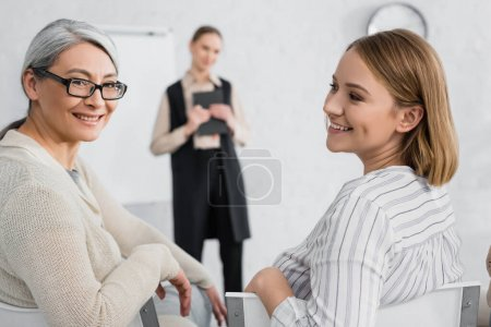 happy businesswoman looking at asian colleague during lecture