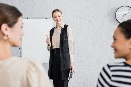 Foto de Altavoz feliz mostrando el pulgar hacia arriba y mirando a las mujeres de negocios interracial en primer plano borrosa - Imagen libre de derechos
