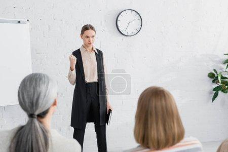 Photo pour Orateur sérieux tenant un cahier et regardant le public des femmes pendant le séminaire - image libre de droit