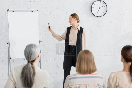 cheerful speaker looking at blank flipchart near woman during seminar on blurred foreground