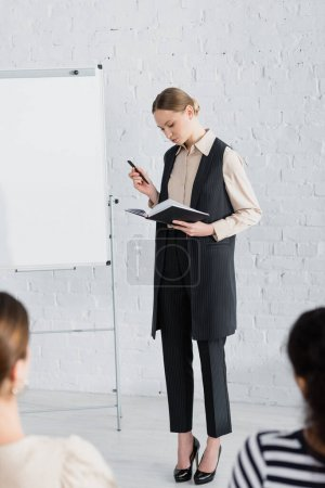 Photo for Young speaker looking at notebook while standing near flipchart and women on blurred foreground - Royalty Free Image