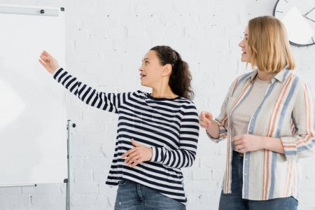 african american businesswoman pointing with hand at flipchart near colleague in meeting room