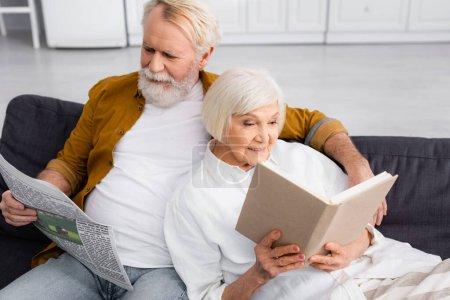 Uśmiechnięta para czytająca książki i wiadomości na kanapie w domu