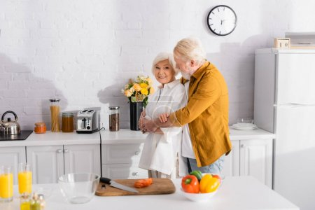 Photo for Elderly man hugging smiling wife near cutting board and fresh vegetables on blurred foreground - Royalty Free Image