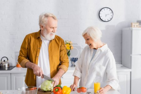 Photo for Man cutting cabbage near fresh vegetables and smiling wife with orange juice in kitchen - Royalty Free Image