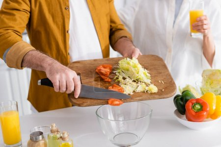 Cropped view of senior man pouring fresh vegetables in bowl near wife with orange juice on blurred background