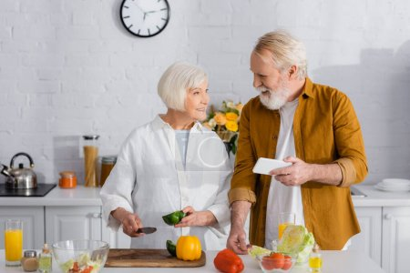 Senior man holding smartphone near smiling wife with knife and paprika in kitchen