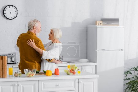 Photo for Senior couple embracing near fresh vegetables and orange juice in kitchen - Royalty Free Image