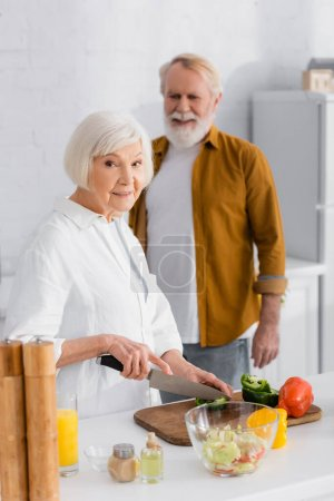Photo pour Femme âgée regardant la caméra tout en coupant paprika près de mari sur fond flou - image libre de droit