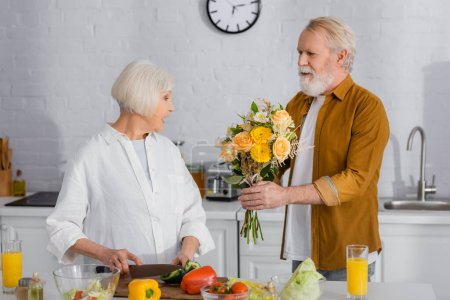 Senior man presenting flowers to wife cutting vegetables in kitchen