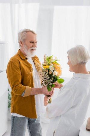 Lächelnder Senior überreicht Frau Blumenstrauß auf verschwommenem Vordergrund in Küche