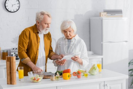 Senior couple using digital tablet while cooking in kitchen