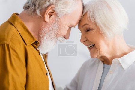 Cheerful senior woman standing near husband at home