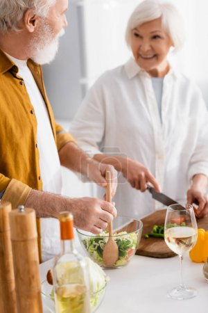 Photo for Elderly man mixing fresh salad near wine and smiling wife on blurred background - Royalty Free Image