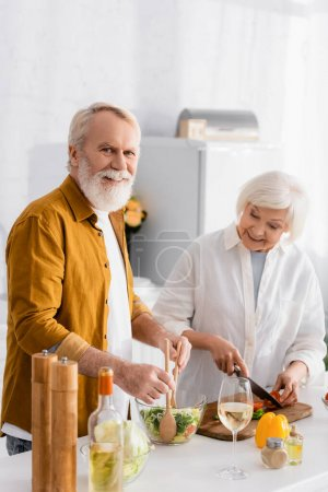 Photo for Senior man smiling at camera while mixing salad beside wife and wine on kitchen table - Royalty Free Image