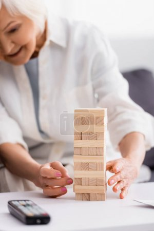 Blocks wood tower game near senior woman and remote controller on blurred foreground