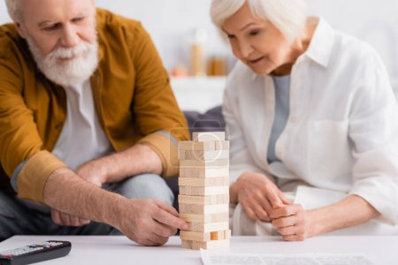 Blocks wood tower game near elderly couple on blurred background in living room