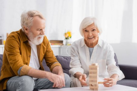 Smiling senior woman playing blocks wood tower game near husband on couch