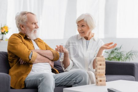 Senior woman talking with husband near blocks wood game on blurred foreground