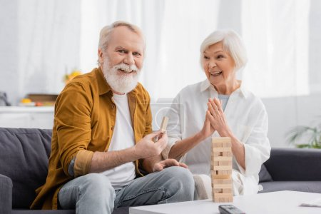 Photo for Senior man holding part of blocks wood game near cheerful wife in living room - Royalty Free Image