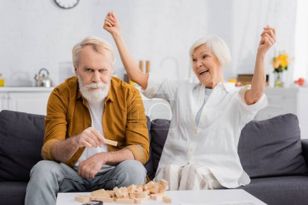 Photo for Excited senior woman looking at husband holding part of blocks wood game - Royalty Free Image