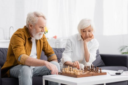 Photo for Pensive elderly couple playing chess near remote controller on blurred background - Royalty Free Image
