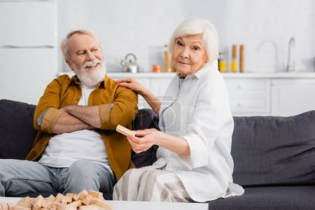 Photo for Senior woman holding part of blocks wood game near cheerful husband on couch - Royalty Free Image