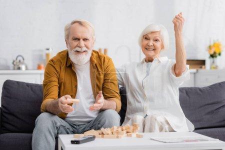 Elderly man holding block of wood tower game near wife showing yeah gesture