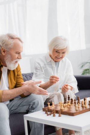 Photo pour Femme âgée souriante assise près des échecs à bord et mari pointant la main sur le premier plan flou - image libre de droit