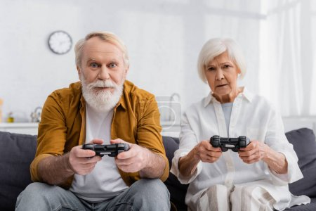 KYIV, UKRAINE - DECEMBER 17, 2020: Elderly couple playing video game at home